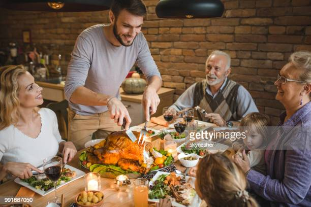 happy extended family talking on thanksgiving dinner at dining table. - roast dinner stock pictures, royalty-free photos & images