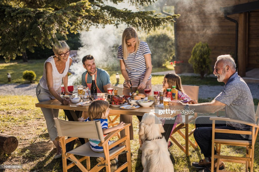 Happy extended family talking while having their lunch in the front yard. : Stock Photo