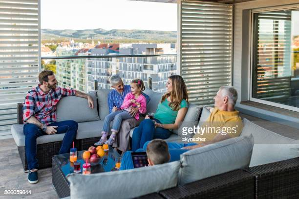 happy extended family talking while relaxing on a penthouse patio. - penthouse girls stock pictures, royalty-free photos & images