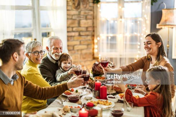 happy extended family toasting during thanksgiving lunch at home. - national holiday stock pictures, royalty-free photos & images