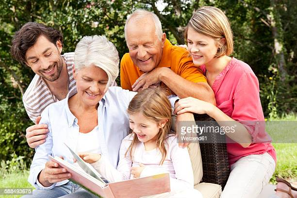 Happy extended family with book outdoors