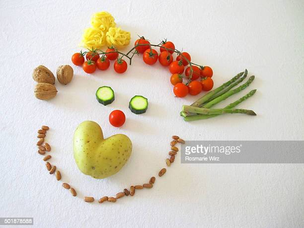 Happy face composed of colorful raw vegetables, seeds and pasta