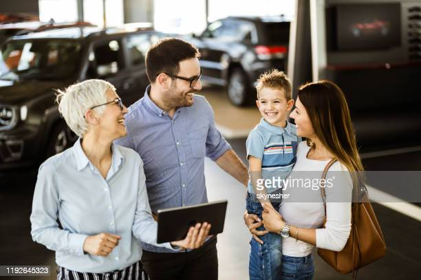 happy family and car salesperson using touchpad in a showroom. - touchpad stock pictures, royalty-free photos & images