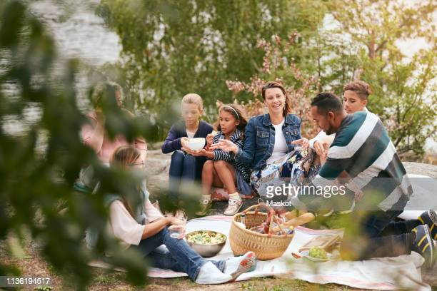 happy family and friends having food on lakeshore in park - picknick stock-fotos und bilder