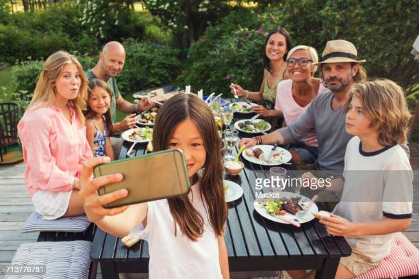 Happy family and friends looking while girl taking selfie from mobile phone at back yard during garden party