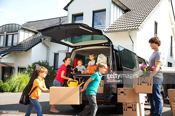 Happy family at driveway carrying cardboard boxes