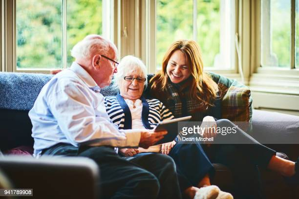 happy family at home using digital tablet - visit stock pictures, royalty-free photos & images