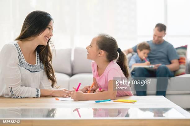 lycklig familj hemma med barnen gör sina läxor och föräldrar övervaka - family at home bildbanksfoton och bilder