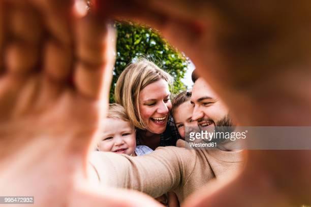happy family behind finger frame - familie mit zwei kindern stock-fotos und bilder
