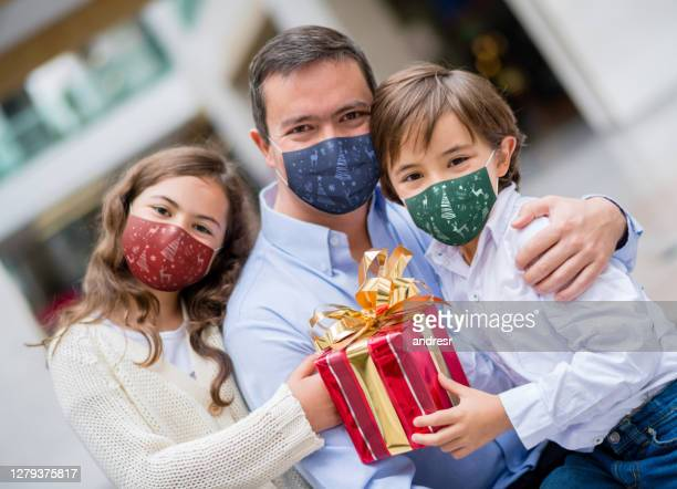happy family buying christmas gifts at the mall wearing facemasks - biosecurity stock pictures, royalty-free photos & images