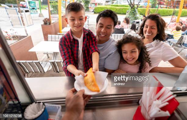 happy family buying food at an amusement park - empanada stock pictures, royalty-free photos & images