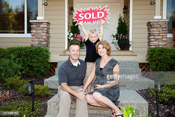 Happy Family buys a new home son holds sold sign