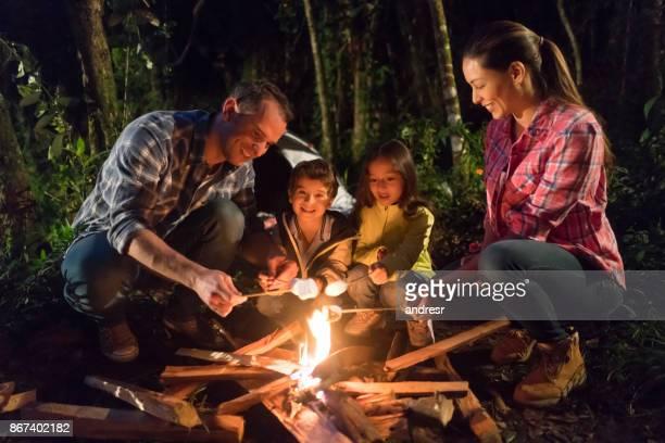 幸せな家族のキャンプと焚き火でマシュマロを融解 - 焚き火 ストックフォトと画像