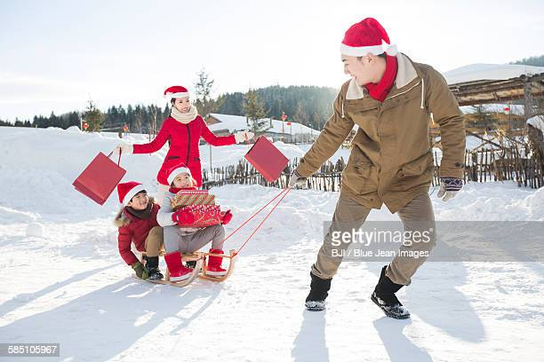 Happy family carrying Christmas Presents with sled