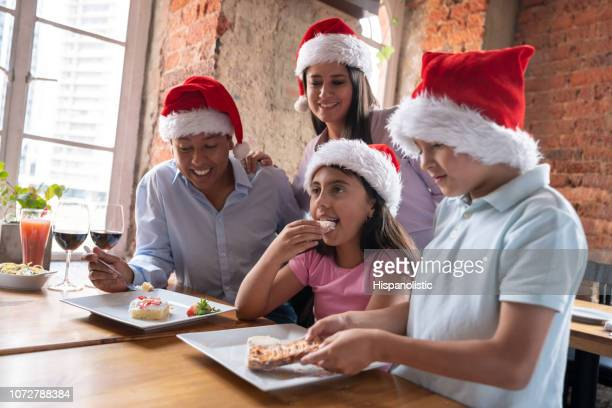 happy family celebrating christmas and eating desserts - hispanolistic stock photos and pictures