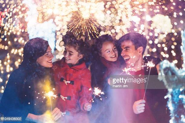 happy family celebrating christmas - fireworks stock pictures, royalty-free photos & images