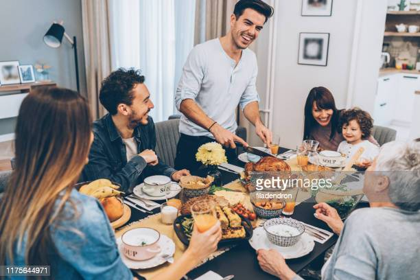 happy family celebrating thanksgiving day - large family stock pictures, royalty-free photos & images