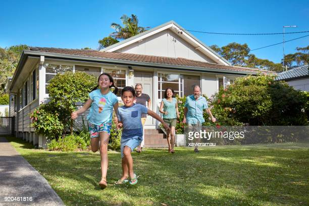 happy family chasing children in lawn - sydney chase stock pictures, royalty-free photos & images