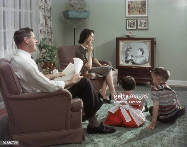Happy family cheerfully sits in their living room and watches a televisied clown and puppet show, 1957. The father holds an newspaper open to the...