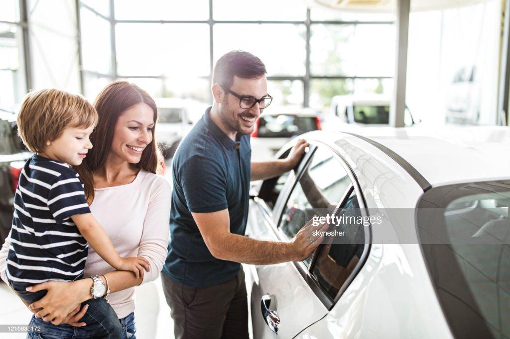 Famiglia felice che sceglie un'auto nuova in uno showroom. : Foto stock