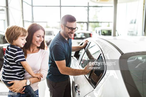 happy family choosing a new car in a showroom. - new stock pictures, royalty-free photos & images