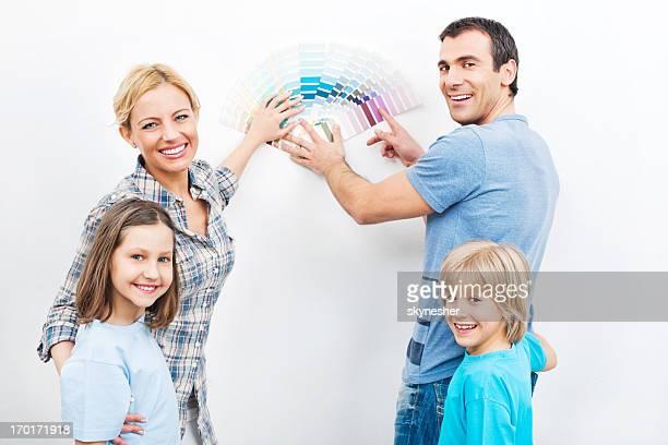 Heureuse famille choisissant de couleur pour le mur