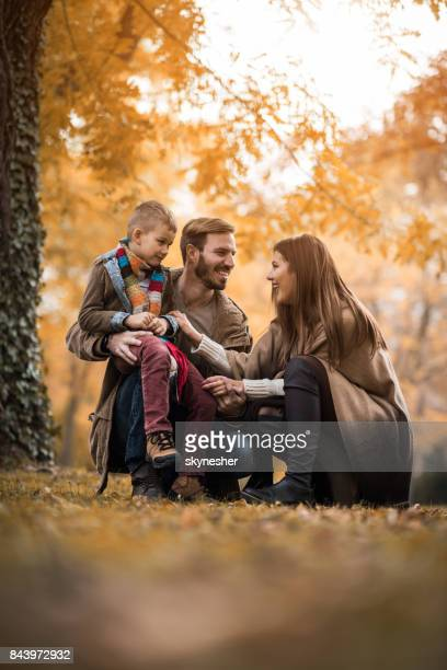 Happy family communicating while enjoying in autumn day at the park.