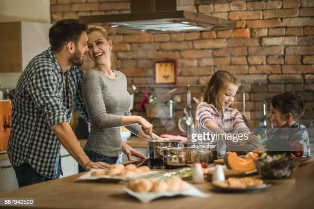 família feliz cooperando ao fazer o almoço na cozinha. - cozinhando - fotografias e filmes do acervo