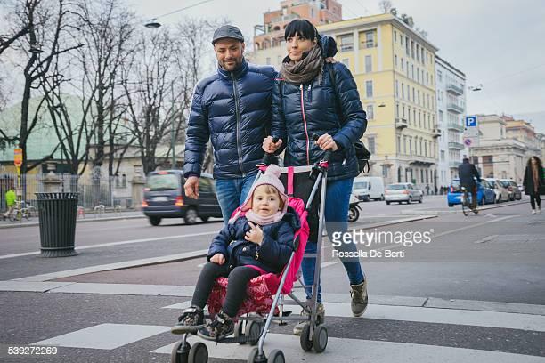 Famille heureuse en traversant la rue