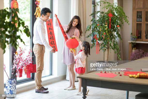Happy family decorating their house for Chinese New Year