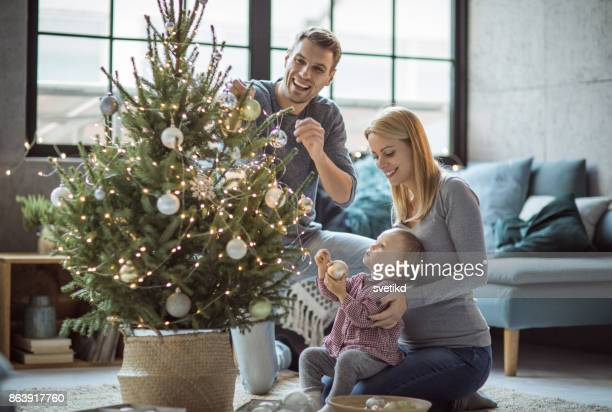 Happy family decorating tree
