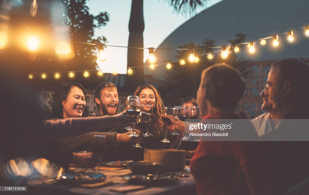 Happy family dining and tasting red wine glasses in barbecue dinner party - People with different ages and ethnicity having fun together - Youth and elderly parents and food weekend activities concept : Stock Photo