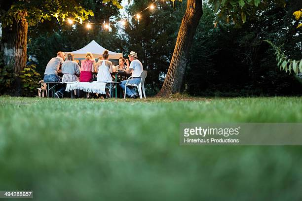 happy family dining in the garden - focus on background stock pictures, royalty-free photos & images