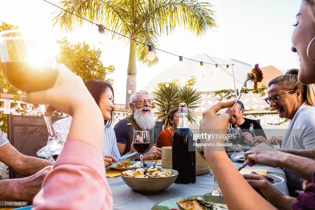 Happy family doing a dinner during sunset time outdoor - Group of diverse friends having fun dining together outside - Concept of lifestyle people, food and weekend activities : Stock Photo