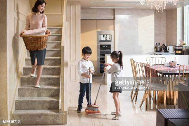 Happy family doing laundry and sweeping at home