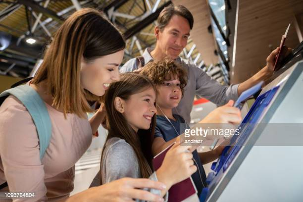 happy family doing the self check-in at the airport - kiosk stock pictures, royalty-free photos & images