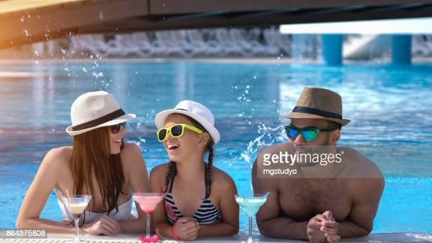 スイミング プールで coktail を飲んで幸せな家族