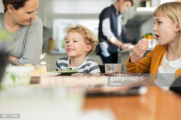 happy family eating breakfast at home - quattro persone foto e immagini stock