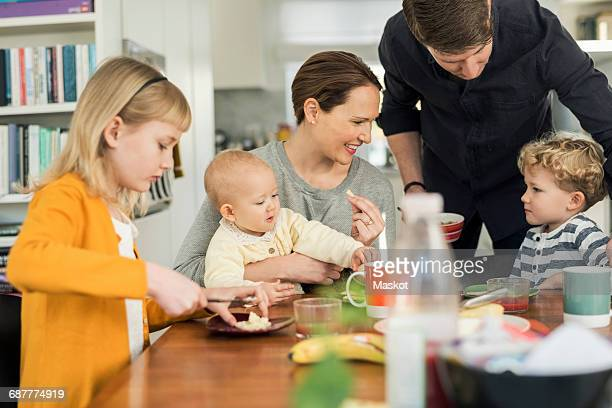Happy family eating breakfast at table in living room