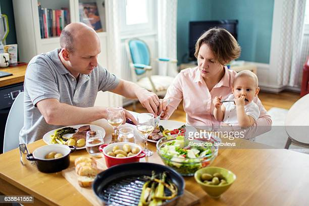 Happy family eating lunch together at home