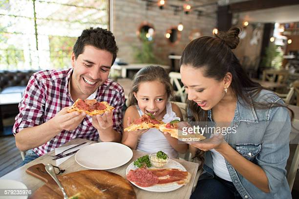 happy family eating pizza at a restaurant - italian culture stock pictures, royalty-free photos & images