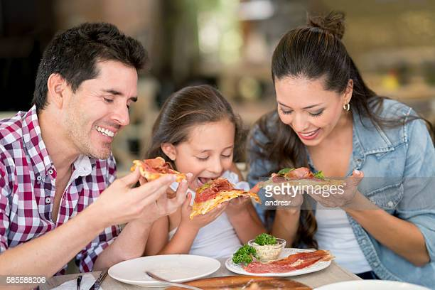 Happy family eating pizza at a restaurant