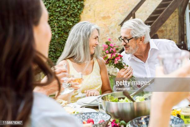 happy family eating together in the garden - gift lounge stock-fotos und bilder