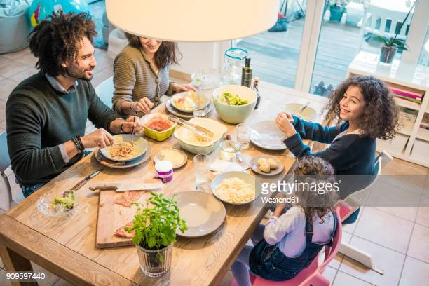 happy family eating together pizza and pasta - family lunch fotografías e imágenes de stock