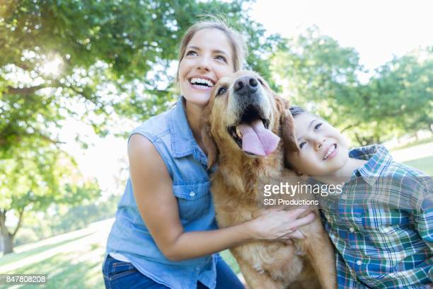 Happy family enjoy time in the park with their dog