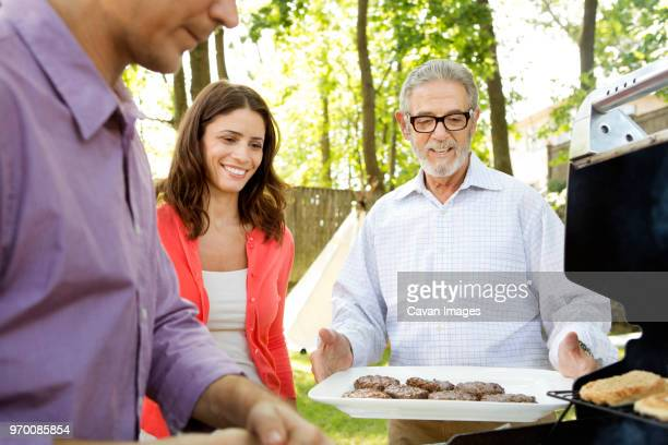 happy family enjoying barbecue grill in lawn - mid adult men stock pictures, royalty-free photos & images