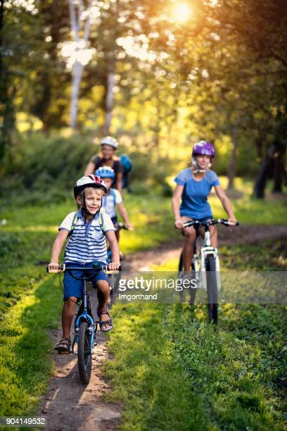 happy family enjoying bicycle ride in park - bicycle stock pictures, royalty-free photos & images