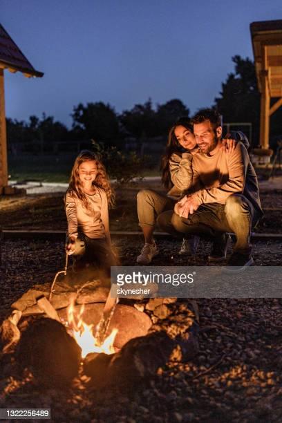 夜は裏庭でたき火で楽しんで幸せな家族。 - 暖炉の火 ストックフォトと画像