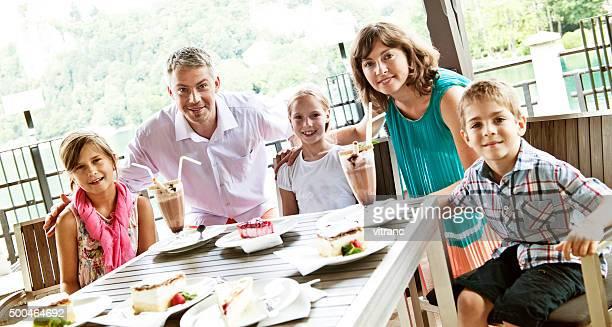 Happy family enjoying ice cream sundae and pastry