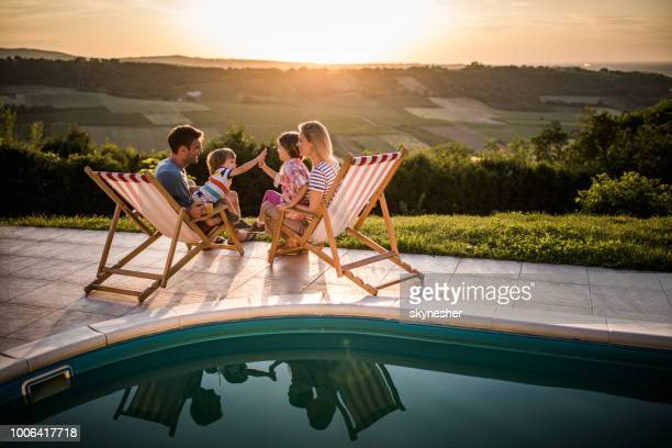 happy family enjoying in deck chairs by the pool at sunset. - furniture stock pictures, royalty-free photos & images